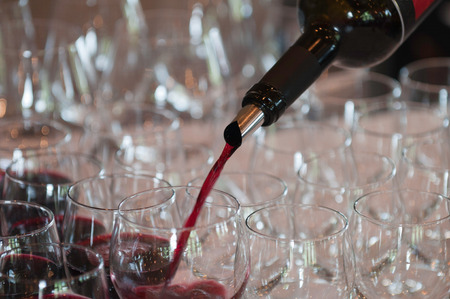 redwine: Pouring red wine at a cocktail party.