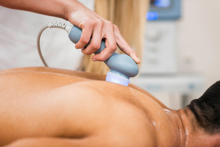 Ultrasound in physical therapy - Therapist using ultrasound to treat patients back Stock Photo