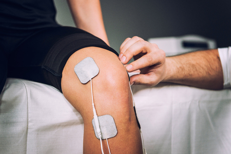 TENS electrodes positioned to treat knee pain in physical therapy Stock Photo