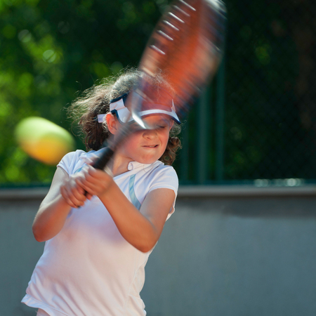 backhand: Tennis talent hits a strong two-handed backhand. Focus set on the face, ball and racquet in motion blur Stock Photo
