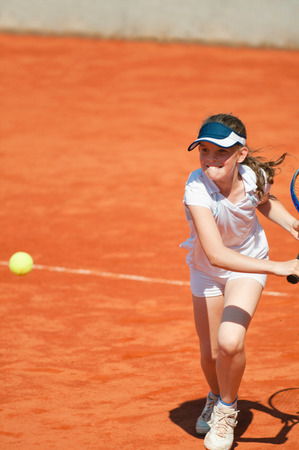 backhand: Young girl on clay court hitting the ball with backhand slice