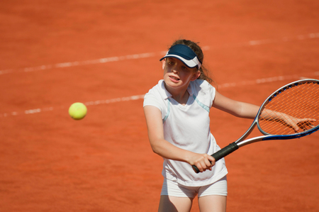 backhand: Young tennis talent hitting the ball with backhand slice Stock Photo