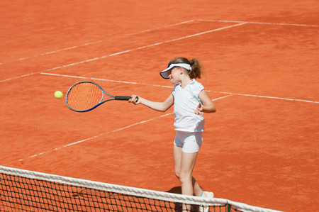 forehand: Junior female tennis player hits forehand. Girl in focus, racket and ball in motion blur. Stock Photo