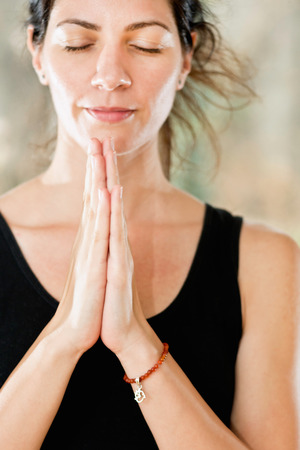Cropped portrait of serene young woman in prayer position, namaste. Focus set on hands with Om sign, soft face. Imagens
