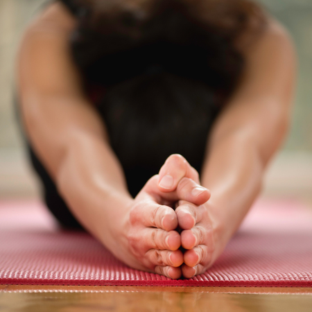 Half Tortoise Yoga Posture, Ardha Kurmasana. Focus on hands, practitioner blurred Stock Photo