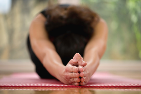 Woman doing Hot Yoga at home - Half Tortoise or Ardha Kurmasana position. Focus on hands