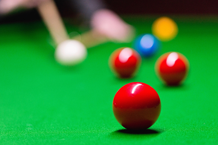 pool hall: Snooker table with red ball in focus
