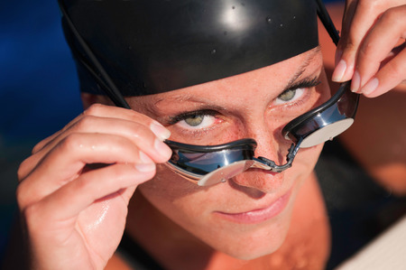 Attractive female taking swimming goggles off and looking up