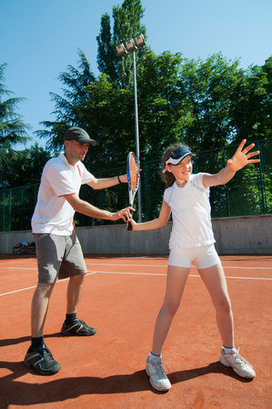 forehand: Tennis coach showing proper forehand technique to a young girl