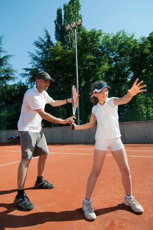 techniek: Tennisleraar tonen goede forehand techniek om een jong meisje