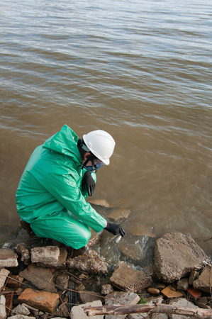 protective suit: Environmentalist in protective suit collecting samples of dirty water