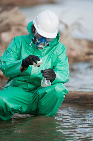 environmentalist: Environmentalist in protective suit taking water samples for analysis