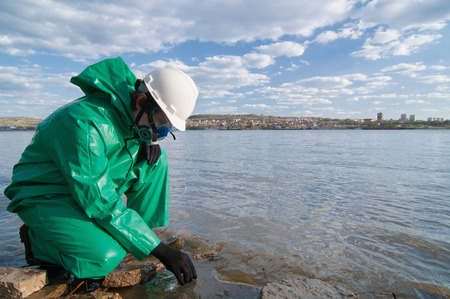 protective suit: Technician in protective suit taking water samples from city reservoir
