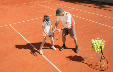 10 year old: Tennis coach with 10 year old talented girl on the court