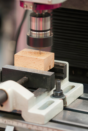 precision: Automated precision drill carving small wooden block