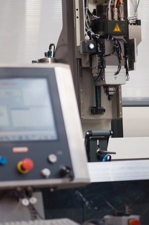 automated tooling: CNC controlled industrial drill with blurred command console in the foreground Stock Photo
