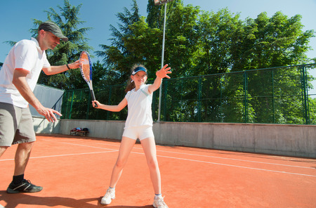 gir: Tennis instructor working with talented gir. Wide angle, polarizing filterl Stock Photo