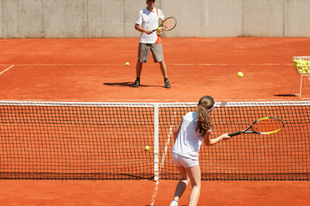10 years girls: Tennis lesson. Instructor teaching young girl voleys on the net. Selective focus. Stock Photo