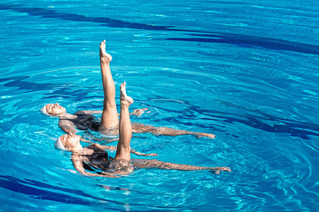 Synchronized swimming pair performing in a swimming pool Stock Photo