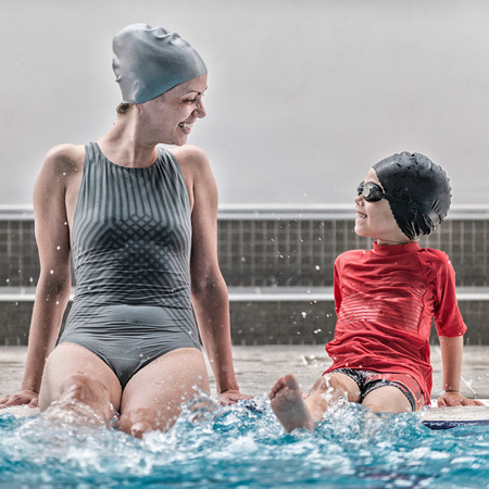 Little child having fun with swimming instructor