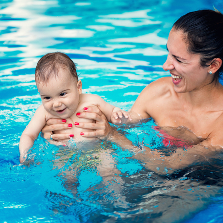 motherly love: Cute baby boy enjoying with his mother in the pool.