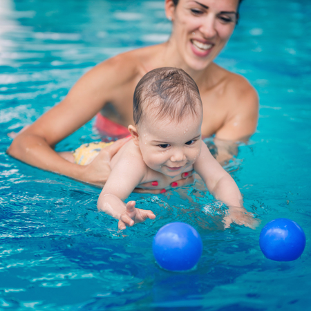 motherly love: Cute baby boy swimming with his mother in the pool. Baby is trying to catch ball