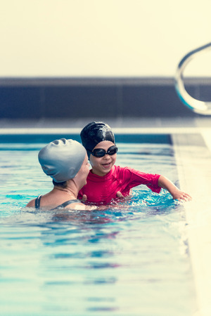 toned image: Swimming class, child with instructor, indoor pool, toned image