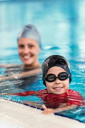 Happy child in the swimming pool, instructor behind