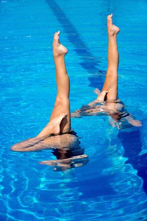 natación sincronizada: Sincronizada rendimiento de los nadadores con las piernas fuera del agua Foto de archivo