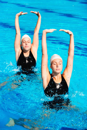 sports training: Synchronized swimmers performing Stock Photo