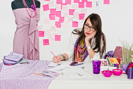 prom dress: Young fashion designer contemplating over a sketch for new prom dress