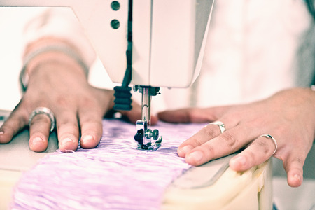 textile image: Sewing machine sewing textile. Close-up, focus on work, toned image Stock Photo