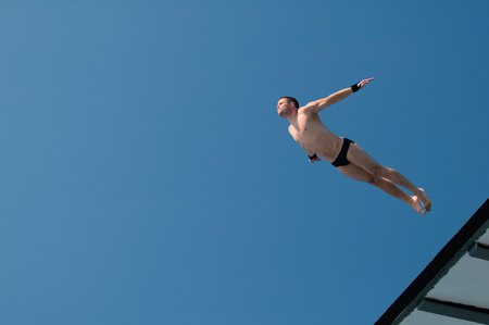 Professional diver caught in flight during attractive old style dive from 10 meter high platform.