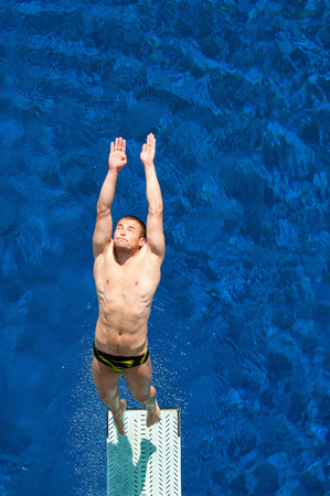 springboard: Competitive male springboard diver caughtwhile leaving the board to twisting back dive