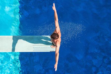 Trampolín competidor de buceo para concentrarse antes de la inmersión. Disparo desde arriba, filtro polarizador Foto de archivo