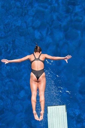 springboard: Mujer competidor de buceo trampolín en el aire. Vista de ángulo alto, filtro polarizador