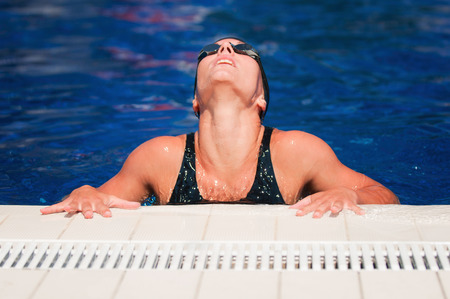 poolside: Female swimmer relaxing at the poolside