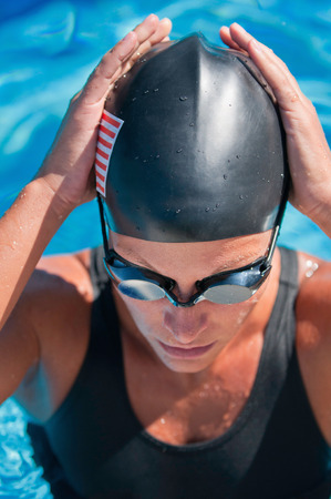 front view: American female swimmer before the race. Focus set on goggles, polarizing filter Stock Photo