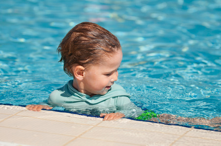 pool side: Little boy hanging on the pool side during swimming class Stock Photo