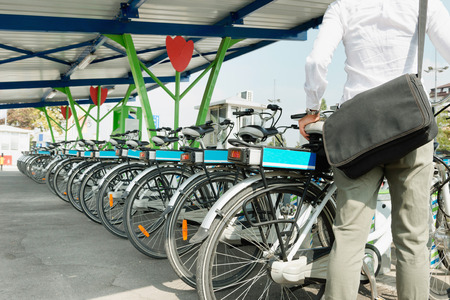 Office worker takes e-bike from bicycle sharing system station