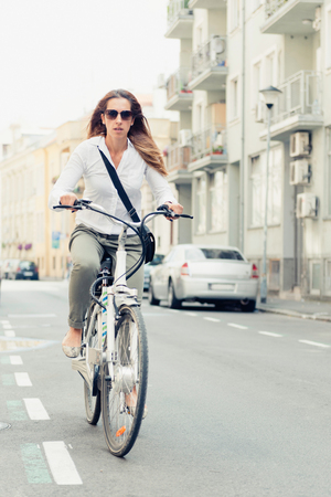 Office worker using e-bike to get to work in a city Stock Photo