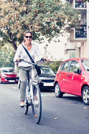 electric system: Young woman using electric bicycle from bicycle sharing system