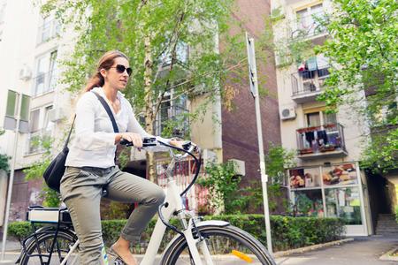 electric motor: E-bike commuter, riding through a city block Stock Photo