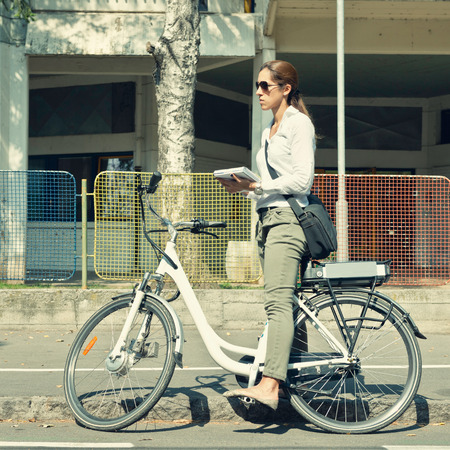 electric motor: Young woman using electric bicycle to get to work in a city Stock Photo