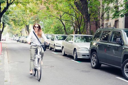 Vrouw rijdt op een elektrische fiets op een straat in de stad