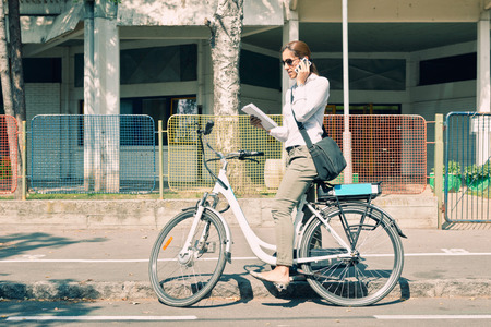 E-bike commuter stops on the street to take a call Banco de Imagens - 54795182