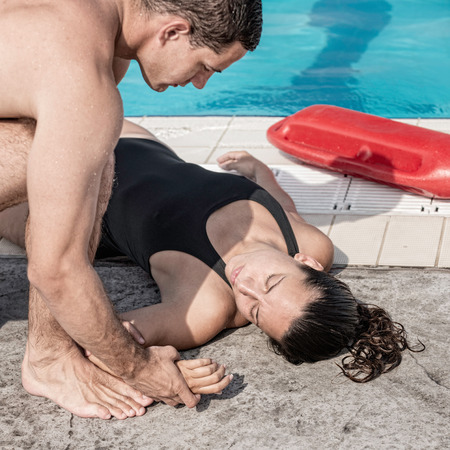 recovery position: Lifeguard checking pulse of a victim after swimming pool accident Stock Photo