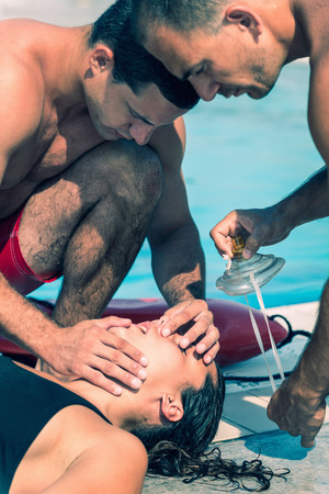 recovery position: Lifeguards practicing CPR, checking air passage on a victim. Toned image
