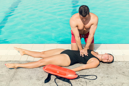 recovery position: Lifeguard doing resuscitation procedure. Toned image