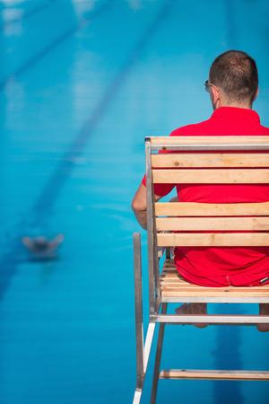 Lifeguard in chair, overlooking swimming pool 版權商用圖片